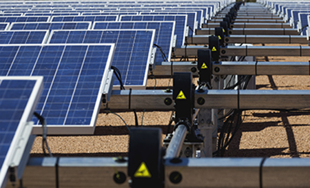 Rows of solar panels at a large solar farm. Showing the hardware that connects them and controls their movement following the sunlight.